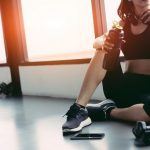 young-Woman-Having-Protein-Drink-Against-Window-In-Gym